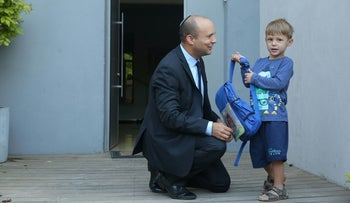 Education Minister Naftali Bennett with one of his four children on the first day of the 2016-2017 school year.