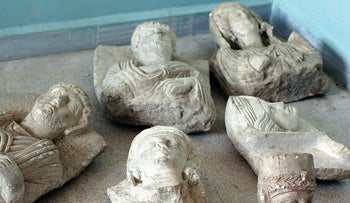 """This image posted on a militant website by the Aleppo branch of the Islamic State group on Friday, July 3, 2015, which has been verified and is consistent with other AP reporting, shows items that the group claims are six smuggled archaeological pieces from the historic central town of Palmyra. An IS statement says the busts were found when the smuggler was stopped at a checkpoint and was later referred to an Islamic which ordered that they be destroyed and the man be whipped. Arabic on the caption reads, """"a collection of smuggled statues was destroyed."""""""