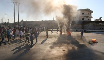 People gather near burning tyres during a demonstration against forces loyal to Syria's President Bashar al-Assad and calling for aid to reach Aleppo, Syria, September 14, 2016.