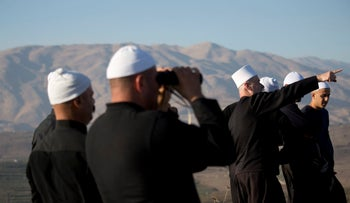 Druze men on the Israeli side of the Golan Heights watch fighting across the border between forces loyal to Syrian President Assad and rebels.
