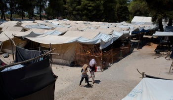 Two young girls walk among tents at Ritsona refugee camp north of Athens.