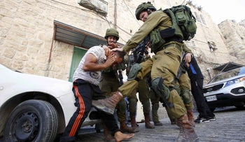 An Israeli soldier kicks a Palestinian man in Hebron, September 20, 2016.