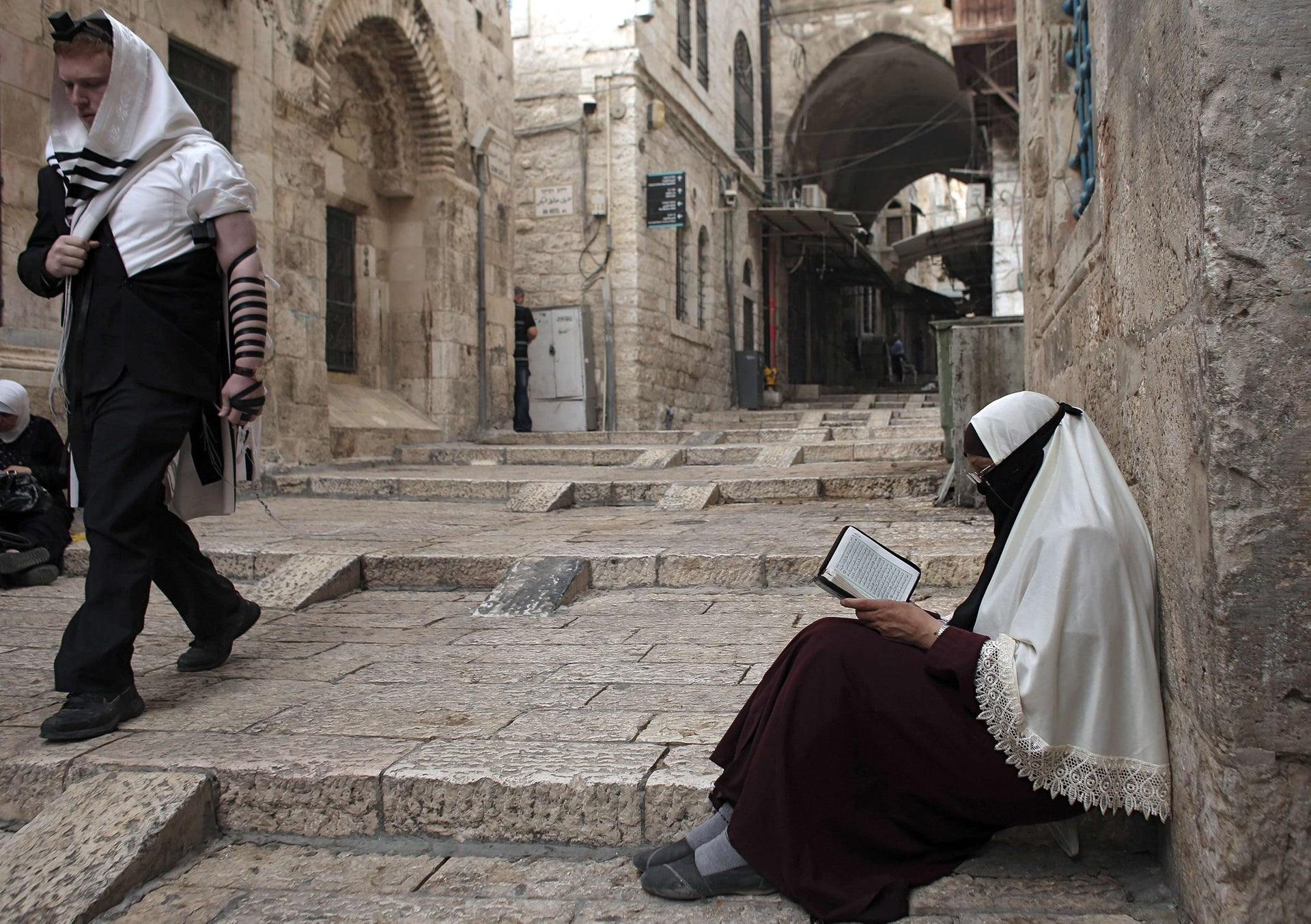 A Palestinian woman belonging to a group who call themselves Murabitat reads a copy of the Kuran, Islam's holy book, as a Jewish Orthodox man walks past her in Jerusalem's Old City on September 10, 2015. Israeli Defence Minister Moshe Yaalon announced on September 9 that he has outlawed The Murabitat (for females) and Murabitun groups which are made up of east Jerusalem Palestinians and Israeli Arabs, some of whom are funded by the Islamic Movement's radical northern wing, who confront Jewish visitors to the volatile Al-Aqsa mosque complex, considered Islam's third holiest shrine. Under the new legal conditions, anyone who organises, finances or participates in the groups' activities could face trial. Non-Muslims are allowed to visit the compound, but Jews are forbidden from praying or displaying national symbols for fear of triggering tensions with Muslim worshippers.