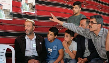 Kayed Rajabi, father of Muhammad, in the mourning tent in Hebron with his sons.