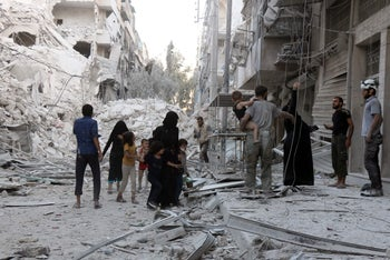 A Syrian family leaves the area following a reported airstrike on September 23, 2016, on the al-Muasalat area in the northern Syrian city of Aleppo.