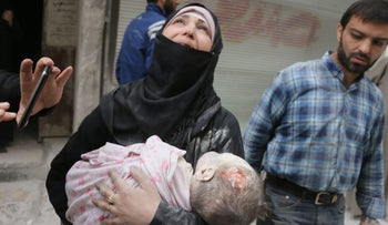 A Syrian woman carries the body of her infant after he was retrieved from under the rubble of a building following an airstrike on September 23, 2016, on the al-Muasalat area in Aleppo, Syria.