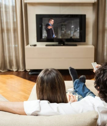 A young couple watching TV together.
