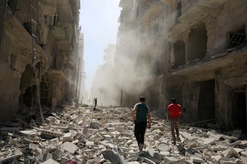 Men inspect the damage after an airstrike on the rebel held al-Qaterji neighborhood of Aleppo, Syria September 25, 2016.
