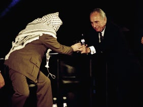 Shimon Peres pours water into a glass and hands it to Palestinian leader Yasser Arafat at the UNESCO in Paris, France, February 18, 1995.