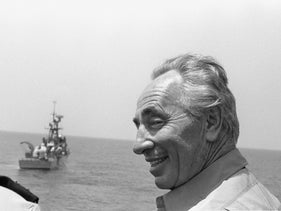 An undated photo of Shimon Peres with a missile ship in the background.