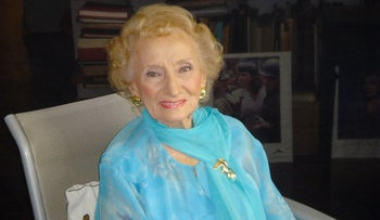 Ruth Gruber in 2007, with short dyed blonde hair, gold earrings and pin, and gauzy blue shirt.