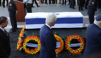 Former U.S. President Bill Clinton next to the coffin of former President Shimon Peres, at the Knesset plaza on September 29, 2016.
