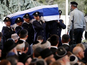 The flag-draped coffin of former President Shimon Peres is carried by an honor guard at the start of his funeral ceremony.