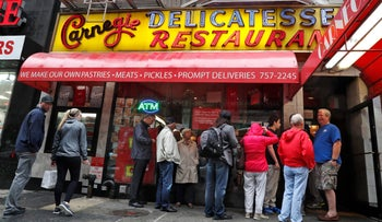 Lunch time customers line up outside the Carnegie Deli, Friday, Sept. 30, 2016, in New York.