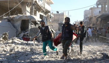 Syrian volunteers carry an injured person following government airstrikes on the rebel-held neighborhood of Heluk in Aleppo, on September 30, 2016.
