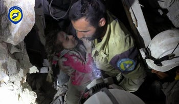 Photo provided by Syrian Civil Defense shows a rescue worker carrying a child pulled out from the rubble of after airstrikes hit the al-Shaar neighborhood in Aleppo, Syria, Sept. 28, 2016.