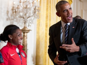 U.S. President Barack Obama leans over to speak to Olympics gymnast Simone Biles at the White House on September 29, 2016.