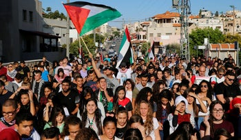 Israeli Arabs carry Palestinian flags during a march in the northern town of Sakhnin, October 1, 2016.