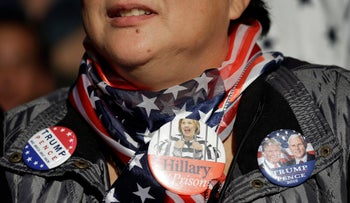 A woman listens as Republican presidential candidate Donald Trump speaks at a rally, Friday, Sept. 30, 2016, in Novi, Mich.