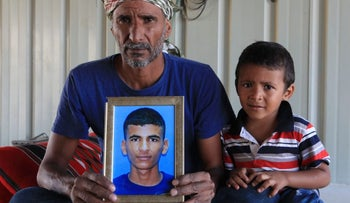 The father and little brother of Mazan Abu Habak hold up a picture of their deceased family member.
