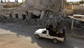 Rebel fighters ride on a pick-up truck past damaged buildings in the northern Syrian rebel-held town of al-Rai, in Aleppo Governorate, Syria, October 5, 2016.