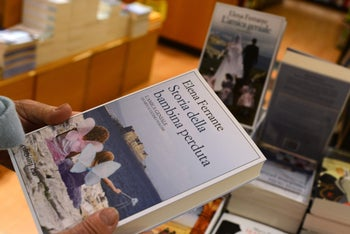 A customer holds a book by Elena Ferrante in a bookstore in Rome on October 4, 2016.