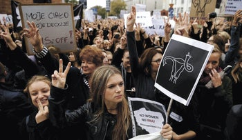 Women gesture as people gather in an abortion rights campaigners' demonstration to protest against plans for a total ban on abortion in front of the ruling party Law and Justice (PiS) headquarters in Warsaw, Poland October 3, 2016