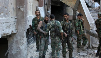 Syrian pro-government soldiers chat as they advance in Aleppo's rebel-held Bustan al-Basha neighbourhood on October 6, 2016.