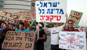 Protest outside the Azrieli Towers in Tel Aviv, against the tycoons and their monopolies, May 25, 2013. Red & blue writing on white sign says: 'Israel, a nation for all its tycoons'. Other signs say, 'Officer, when the bank robs me, come save me'. The octopus bears the name of tycoon Nochi Dankner, with each arm leading to another of his many IDB Group companies, including the cement monopoly Nesher.
