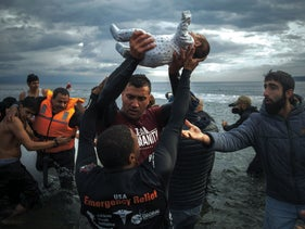 A volunteer holds up a baby as others help migrants and refugees to disembark from a dinghy after their arrival to Lesbos, Greece, November 25, 2015.