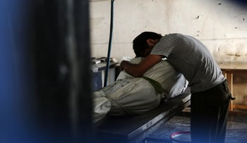 A Syrian man mourns over the body of his father who was killed in air strikes on the rebel-held town of Douma, on the eastern outskirts of the capital Damascus, on October 5, 2016.