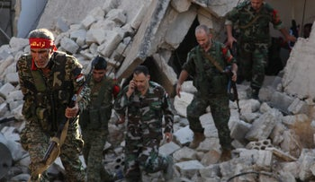 Syrian pro-government soldiers patrol the area of Awijah as they advance in Aleppo's rebel-held neighbourhoods, on October 8, 2016.