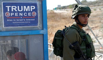 An Israeli soldier stands next to a bus stop covered with a poster from the Israeli branch of the Trump campaign, near the West Bank Jewish Settlement of Ariel October 6, 2016.