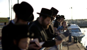 People pray during the Tashlich ritual on the eve of Yom Kippur in Ashdod, October 11, 2016.