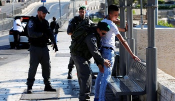 Border policemen perform a body search on a Palestinian youth following a stabbing attack on near Jerusalem's Old City.