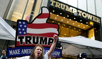 Supporters of Republican presidential nominee Donald Trump stand outside Trump Tower in New York on October 8, 2016.