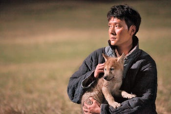 Feng Shaofeng as Chen, with a wolf cub in a scene from 'Wolf Totem.'