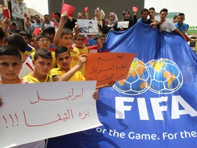 Palestinian youths hold red cards and placards reading in Arabic: 'Israel out of FIFA,' during a demonstration against the Israeli Football Federation in Hebron, May 28, 2015.