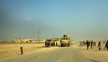 A convoy of armored coalition vehicles passes through a camp for displaced civilians on the road outside Qayara airbase south of Mosul on Tuesday, Aug. 30, 2016.