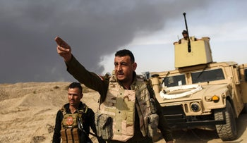 A member of Iraqi forces gestures as troops head to the frontline during an operation to recapture Mosul from ISIS, Qayyarah, Iraq, October 18, 2016.