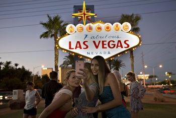 Visitors pose for a selfie in Las Vegas, Nevada, ahead of the presidential debate, October 18, 2016.