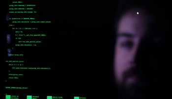 FILE PHOTO: The face of an attendee is reflected in a laptop computer screen alongside code as he participates in the TechCrunch Disrupt London 2015 Hackathon in London, U.K., on Saturday, Dec. 5, 2015.