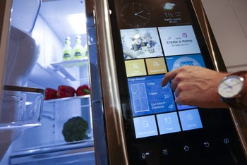 An employee demonstrates a Smart Home fridge at a John Lewis department store in London, April 8, 2016.