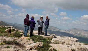 An illustrative photo shows a guide and tourist atop a West Bank hilltop.