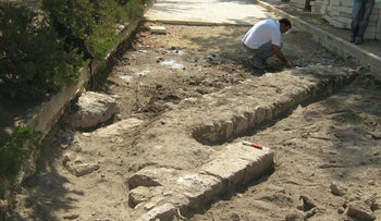 The structure that was uncovered on the northern part of the Temple Mount. A man kneels next to a stone wall protruding from the ground.