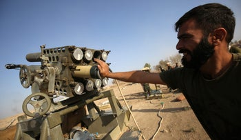 A Shi'ite fighter from the Popular Mobilization Forces prepares missiles to launch on the village of Salmani, south of Mosul, October 30, 2016.