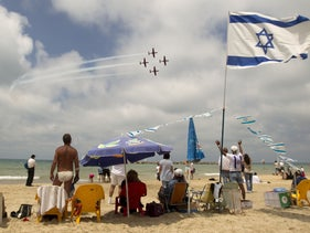 Israelis on the beach in Tel Aviv watch a military show marking Israeli Independence Day, April 26, 2012.