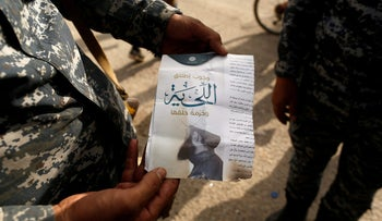 """An Iraqi soldier shows a pamphlet which reads """"Wearing beards is compulsory, shaving is prohibited"""" along a street of the town of al-Shura, which was recaptured from Islamic State (IS) on Saturday, south of Mosul, Iraq October 30, 2016."""