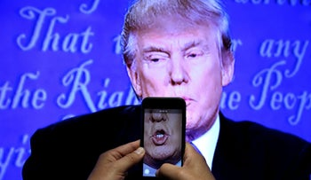 A journalist records Donald Trump speaking during the first presidential debate.