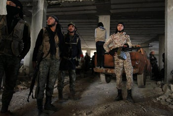 Rebel fighters stand with their weapons inside a building in western Aleppo on November 3, 2016